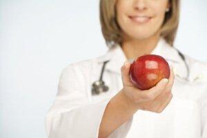 Врач держит яблоко