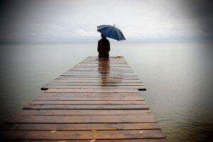 Сидит под зонтом