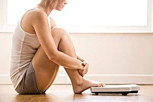 Девушка сидит рядом с весами