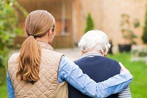 Женщина обнимает старушку