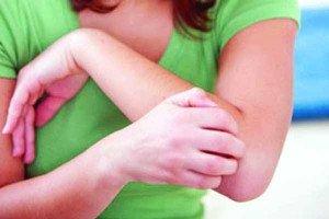 Девушка чешет руку